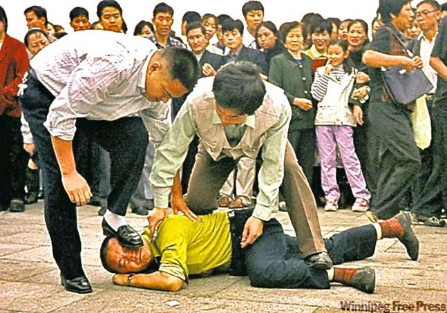 A Falun Gong practitioner overpowered and arrested in Tiananmen Square